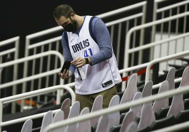A Dallas Mavericks fan takes photographs of Houston Rockets fan cutouts before a NBA game Monday, Jan. 4, 2021, at Toyota Center in Houston. Photo: Yi-Chin Lee/Staff Photographer / © 2021 Houston Chronicle