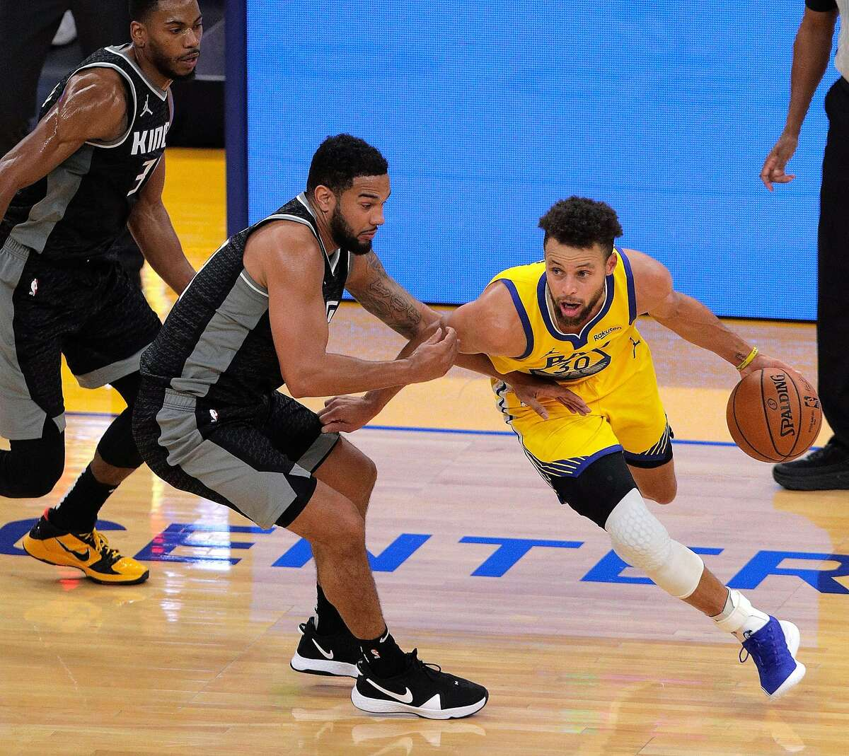 Warriors guard Stephen Curry dribbles around guard Cory Joseph of the Sacramento Kings in the first half of Golden State's win at Chase Center.