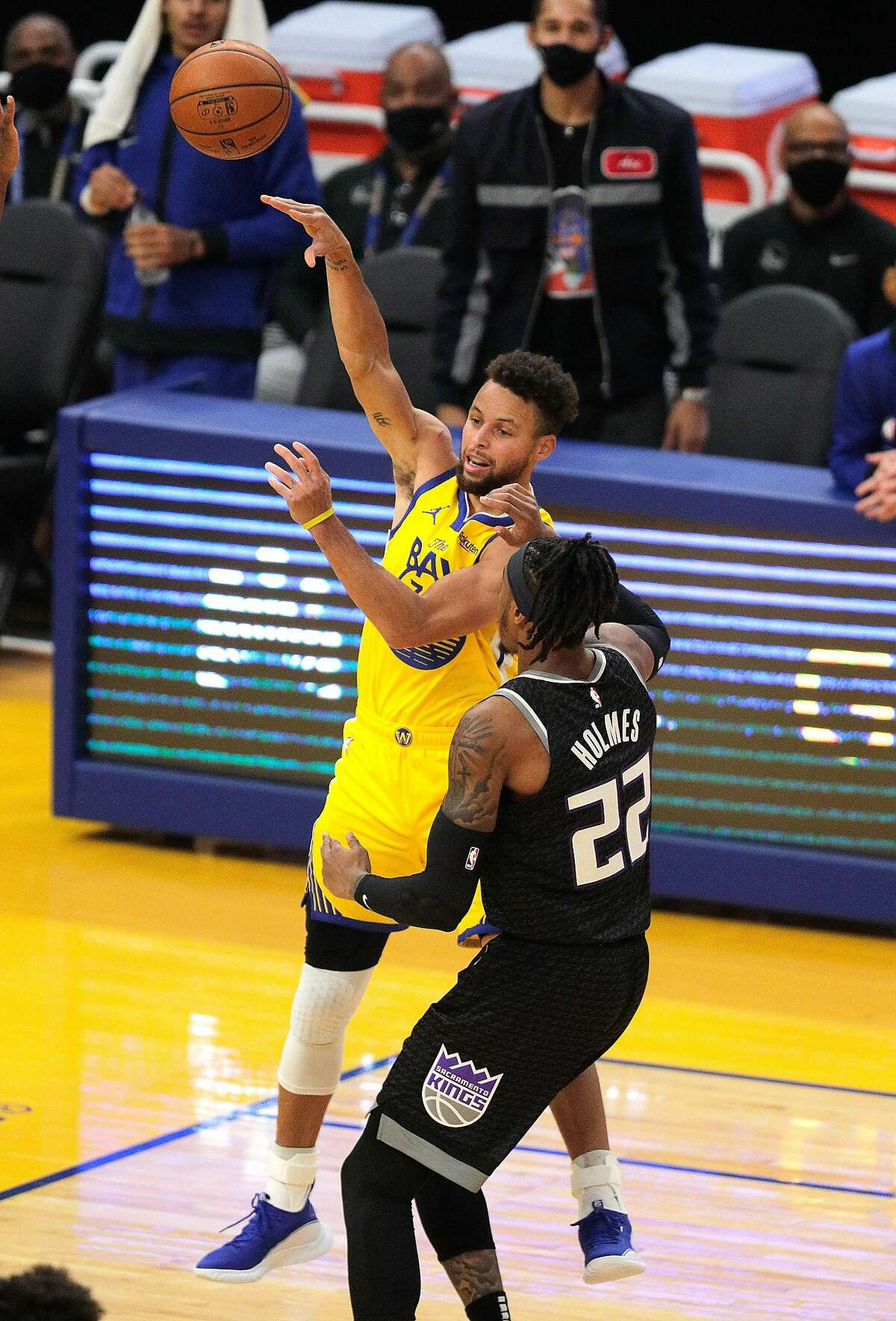 Stephen Curry (30) passes to a teammate defended by Richaun Holmes (22) in the first half as the Golden State Warriors played the Sacramento Kings at Chase Center in San Francisco, Calif., on Monday, January 4, 2021.