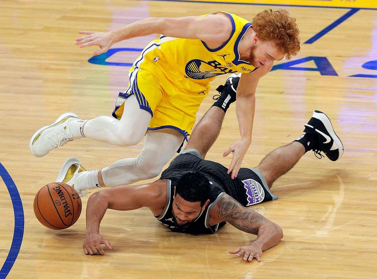 Nico Mannion (2) is fouled by Cory Joseph (9) chasing a loose ball in the second half as the Golden State Warriors played the Sacramento Kings at Chase Center in San Francisco, Calif., on Monday, January 4, 2021.