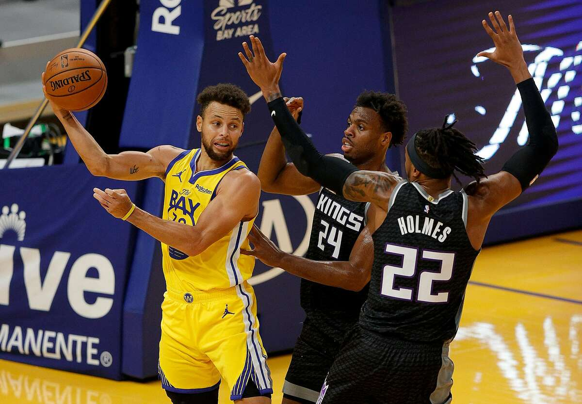 Stephen Curry #30 of the Golden State Warriors looks to pass around Richaun Holmes #22 and Buddy Hield #24 of the Sacramento Kings at Chase Center on January 04, 2021 in San Francisco, California.