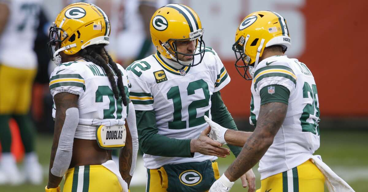 Green Bay Packers quarterback Aaron Rodgers (12) talks with running back A.J. Dillon (28) during warm ups before an NFL football game against the Chicago Bears, Sunday, Jan. 3, 2021, in Chicago. (AP Photo/Kamil Krzaczynski)