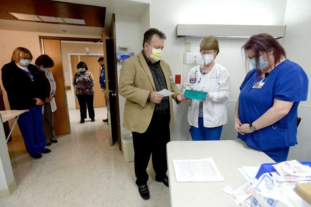 Pastor Rick Roach offers a prayer of blessing over vials of COVID-19 vaccine as infection control nurse Robin Gail Wooten (center) and nurse Andrea Spears prepare to administer the first shots of the Moderna vaccine at Christus of Southeast Texas Jasper Memorial Hospital Tuesday. Photo taken Tuesday, January 5, 2021 Kim Brent/The Enterprise