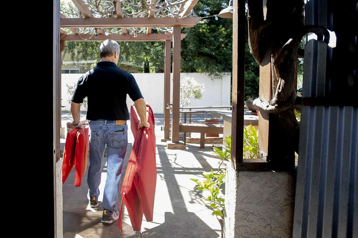 Fume Bistro owner Terry Letson carries cushions to place on outdoor seating for customers at his restaurant in Napa in May before outdoor dining was allowed.