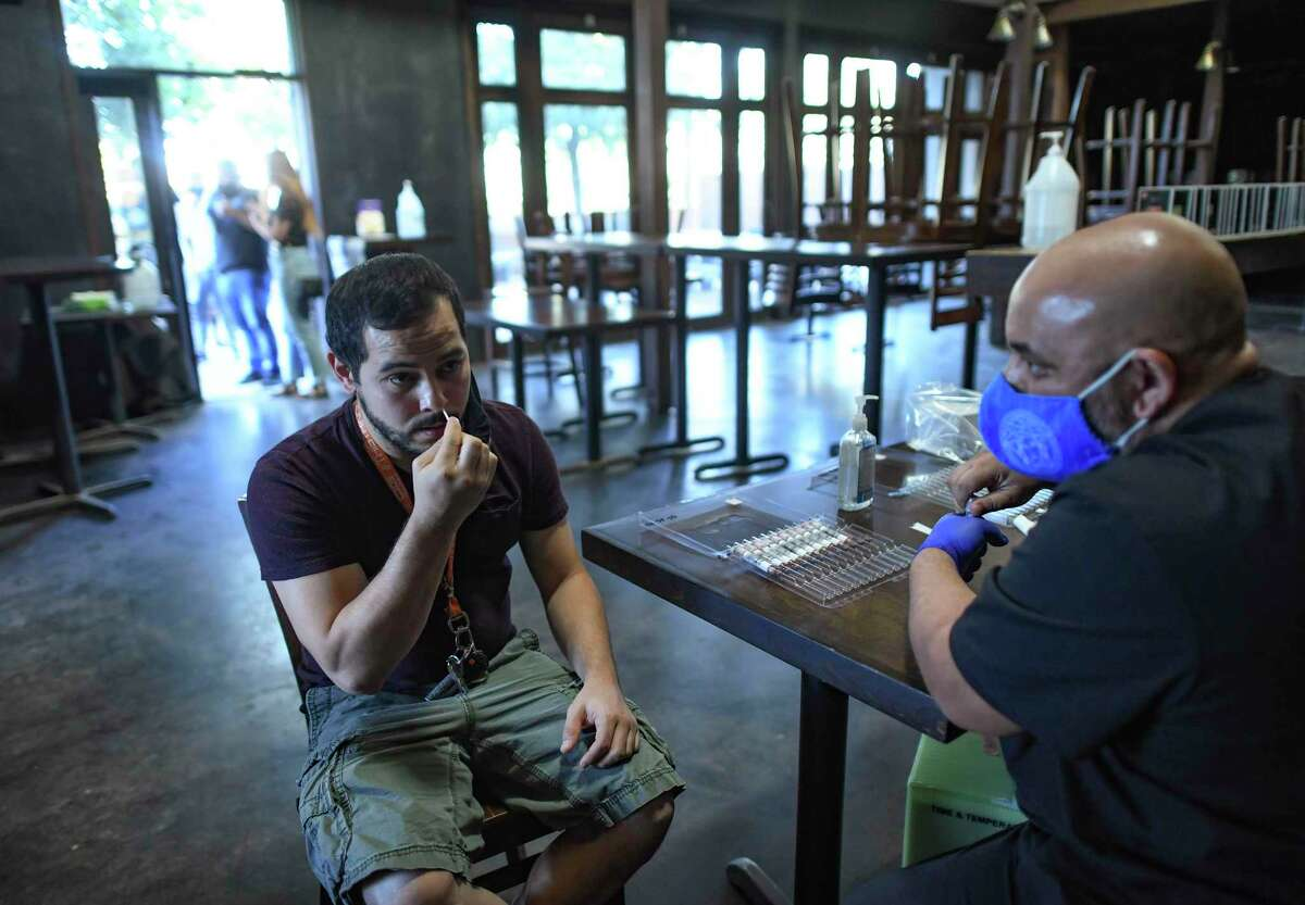 Christian Gabriel swabs his nostrils for a COVID-19 test with the help of David Amrollah through Community Labs at the Hoppy Monk restaurant on Nov. 2.