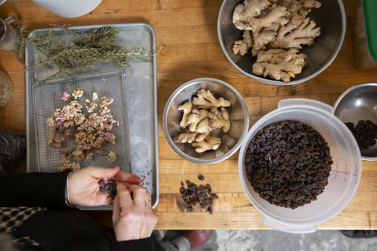 June Taylor painstakingly de-stems raisins she's been dehydrating for Christmas cakes at her kitchen in Berkeley, Calif. on Monday, January 4, 2021. After 17 years in her current space and over 30 years of preserving, June Taylor is going to be closing down her business and kitchen.