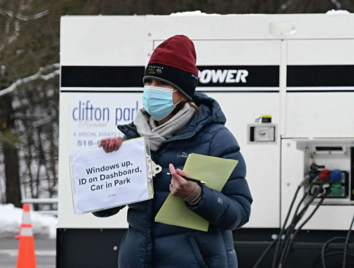 A health care worker holds up a sign to a driver in line at a state testing site set up in Saratoga Spa State Park to provide COVID-19 testing for N. Fox jewelry customers on Monday, Jan. 4, 2021 in Saratoga Springs, N.Y. The first New York case of the U.K. coronavirus strain was detected in a man who works at the jewelry store on Broadway. (Lori Van Buren/Times Union)