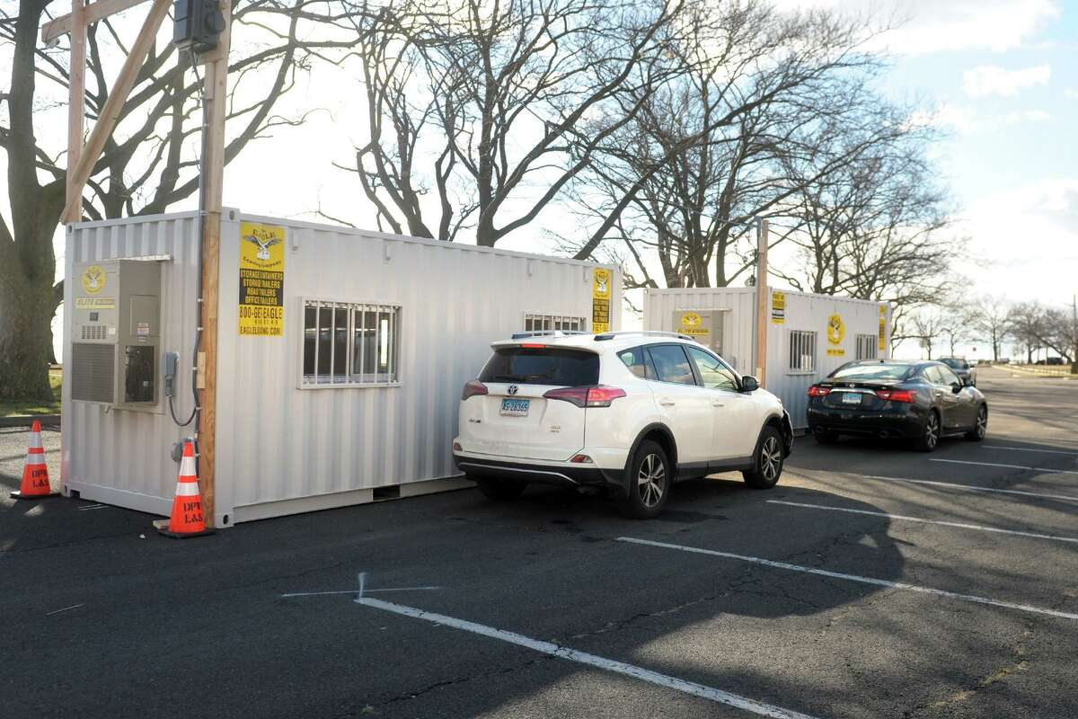 Cars line up next to portable trailers set up for the Connecticut Department of Public Health's new drive-thru testing site at Seaside Park, in Bridgeport, Conn. Jan. 5, 2021.