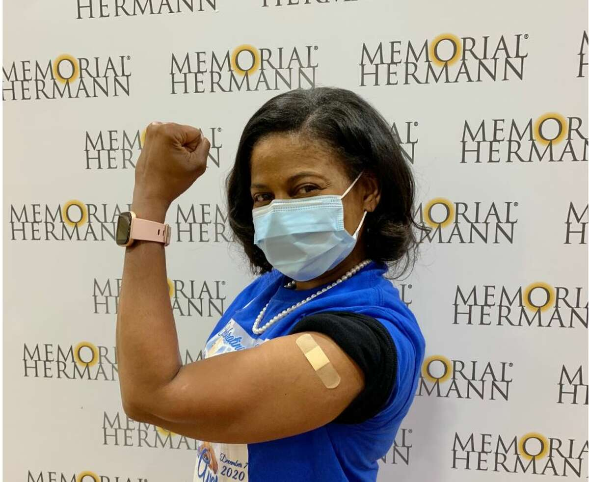 Head of security at Memorial Hermann Brigid Roberson rolls up her sleeve for the vaccine.