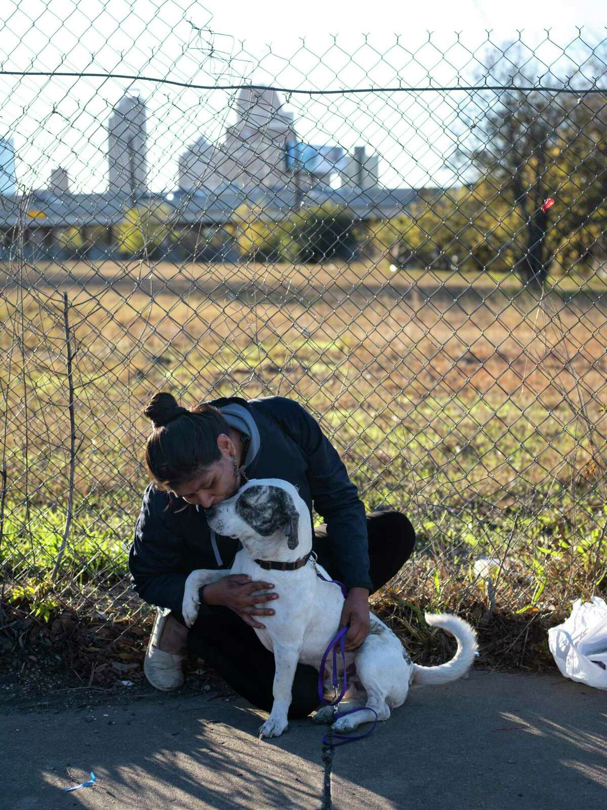 """Rubyann Maldonado talks to her dog, Lockwood, after receiving free veterinary services provided by the nonprofit Hope 4 Hounds at Communities Under the Bridge on Sunday, December 13, 2020. Maldonado says that she found Lockwood two years ago at Lockwood park in San Antonio. Maldonado says that it's tough to feed Lockwood, keep him flea-free and to make sure he doesn't run off while they live together on the streets. """"He has bad separation anxiety,"""" she says, """"but that's my fault because I'm attached to him. He's my support animal. I can't do nothing without him."""" Maldonado appreciated the free services. """"This means the world. This means no one can take him from me,"""" she said, referring to the microchip that Hope 4 Hounds placed in Lockwood, keeping on record that Maldonado is his owner."""