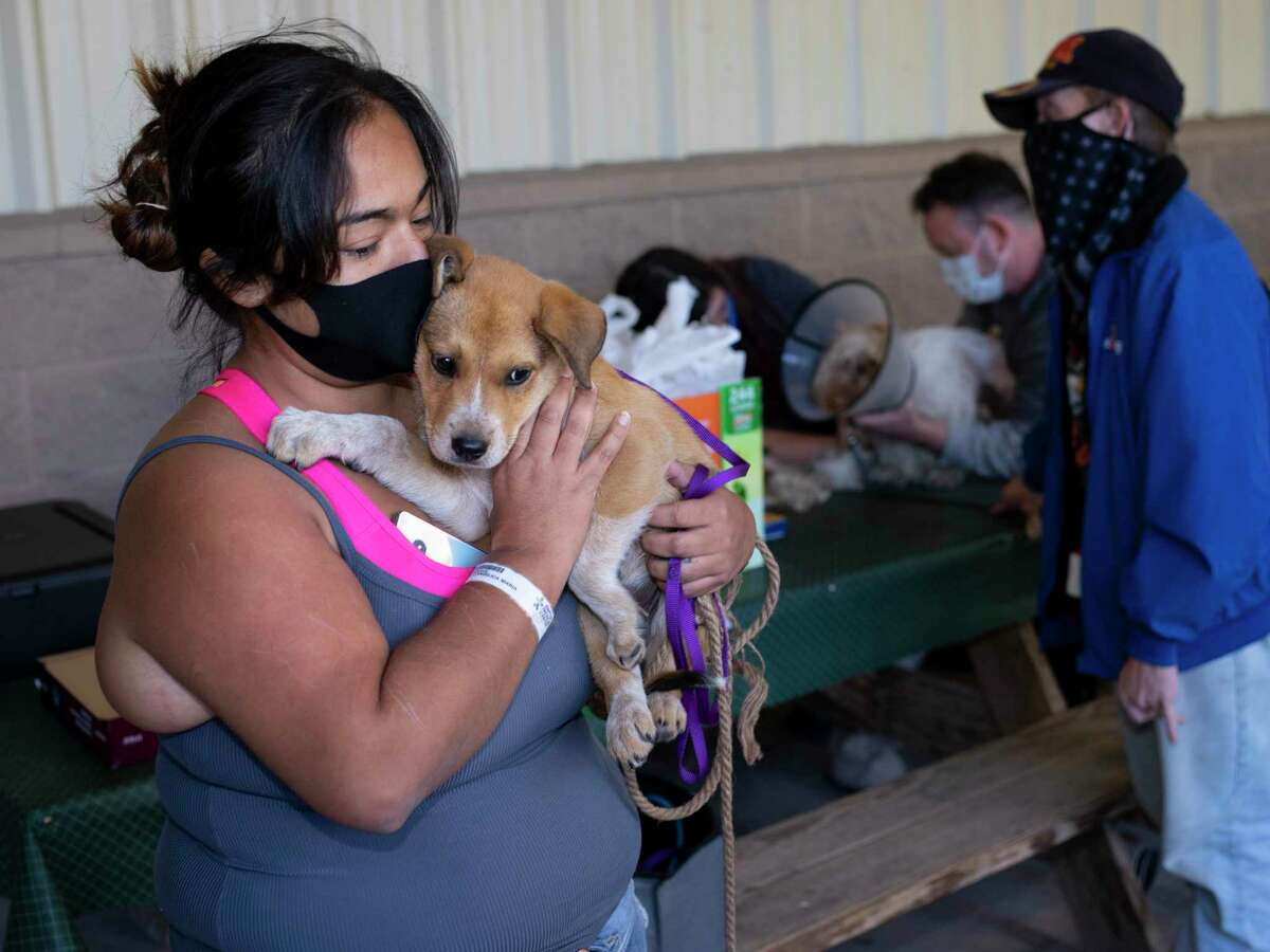 Angelica Scott holds her puppy Lilly who received free veterinary services provided by the nonprofit Hope 4 Hounds at Communities Under the Bridge on Sunday, December 13, 2020. Ross and Jill Powell founded the nonprofit to offer free grooming and veterinary care for pet dogs of men and women living on San Antonio streets.