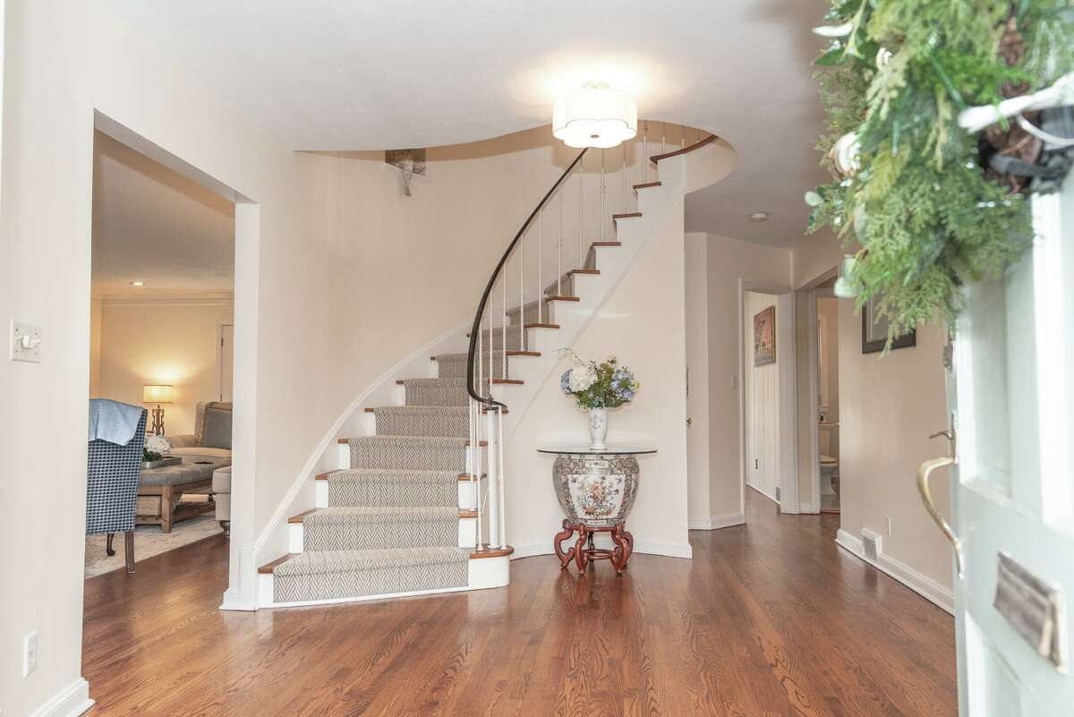 Graceful spiral staircase in the foyer at 139 Northwood Road, Fairfield.
