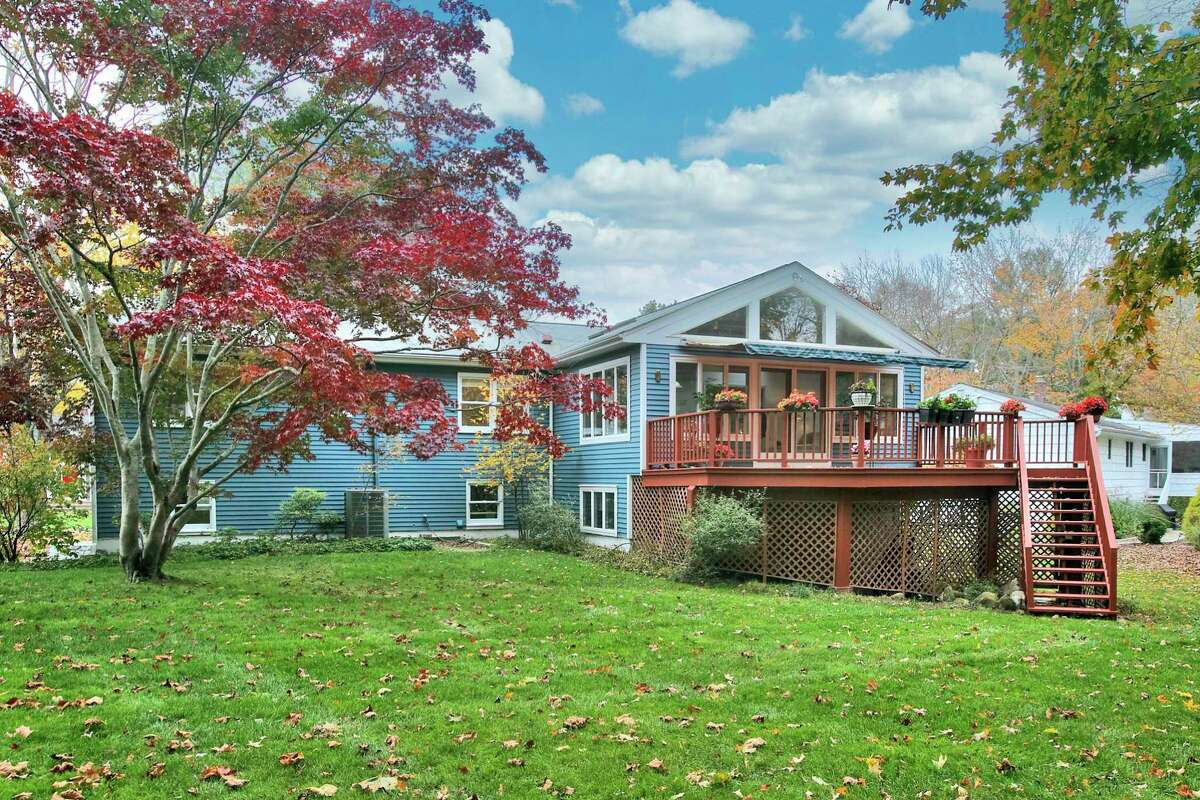 The contemporary house at 6 Peaceful Lane, Westport sits on a level half acre property and features a raised deck.