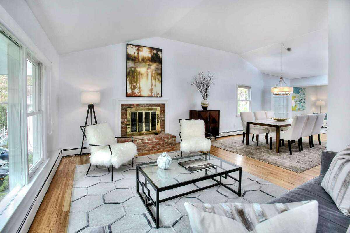 The living room has a fireplace and is open to the dining room at 6 Peaceful Lane, Westport.