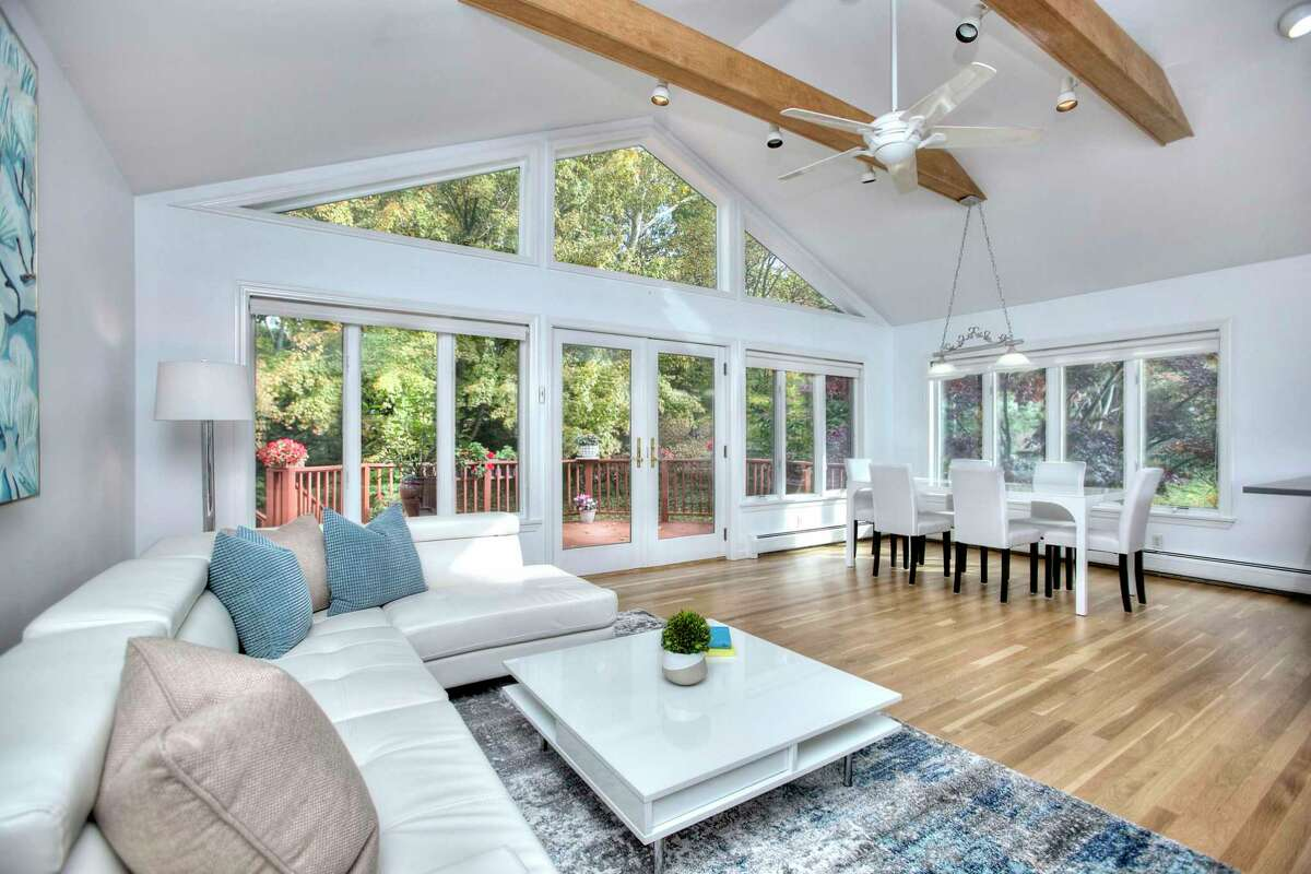The great room at 6 Peaceful Lane, Westport has French doors to the deck. It was built in 1962 but improvements throughout the years, including many recent updates, have provided this 10-room house with many modern conveniences including a newer, designer eat-in kitchen with quartz countertops, an extraordinarily large and bright walk-out lower level with recreation space, and an open floor plan. A carpet of green grass and pachysandra comprises the front lawn, and a tall maple tree stands near the entrance. The front door is flanked by sidelights and a tall transom, which combine with numerous windows to allow an abundant flow of natural light into this house.