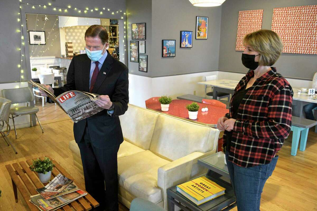 U.S. Sen. Richard Blumenthal, left, stops to look at an old issue of Life magazine during a visit with Anna Llanos, owner of Mothership on Main restaurant. Blumenthal talked with Llanos about her small business and the Paycheck Protection Program. Tuesday morning, January 5, 20201, in Danbury, Conn.
