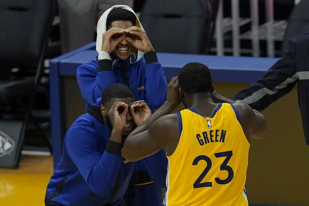 Golden State Warriors forward Draymond Green (23) celebrates with Jordan Poole, top, and Kevon Looney during the first half of Monday's game against the Sacramento Kings.