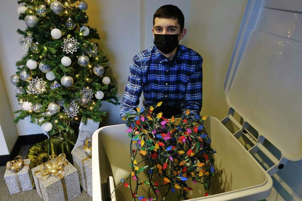 Boy Scout Tyler Michaels, 16, holds a string of lights that were left in one of the recycle bins that he, along with the help of his father, set up at 12 locations throughout the City of Troy, on Tuesday, Jan. 5, 2021, in Troy, N.Y. Lights should be dropped off in one of the bins by January 14th. The recycle bins are located in Troy at city hall, each of the six firehouses, at the Troy Police headquarters, the Rensselaer County office building, the Department of Public Works, Department of Public Utilities, and the main Post Office branch. (Paul Buckowski/Times Union)