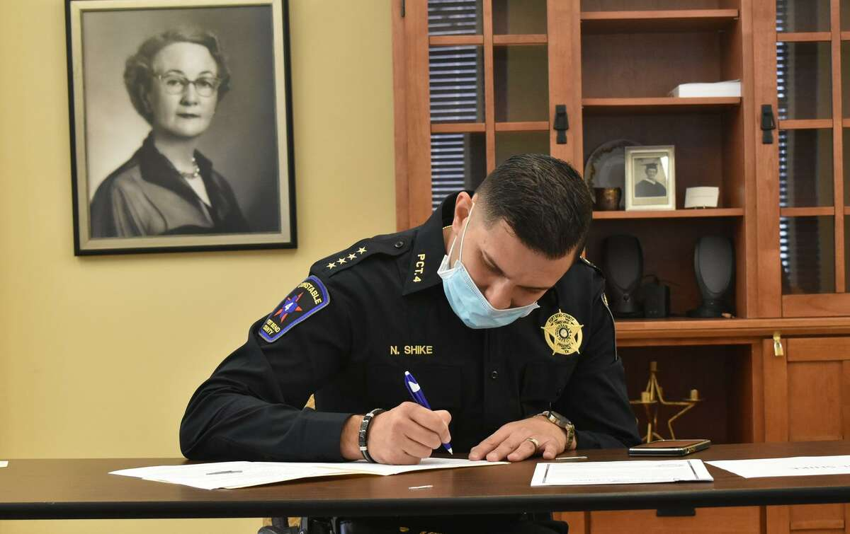 Fort Bend Precinct 2 Constable Nabil Shike signs his paperwork after recently being sworn into service by Fort Bend County Judge KP George.