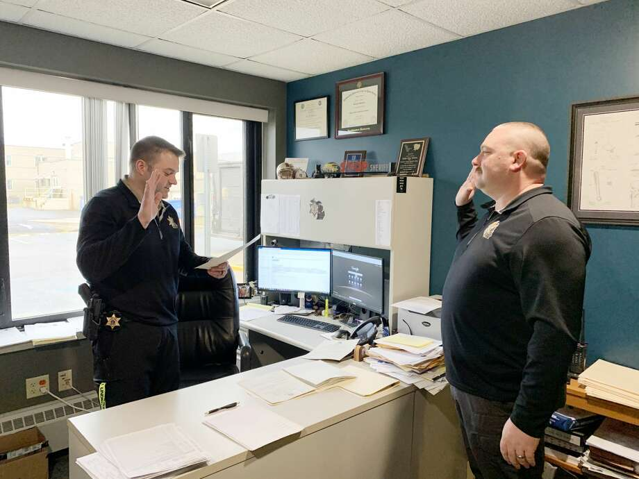 (From left) Manistee County Sheriff Brian Gutowski swears Jason Torrey into office as county undersheriff on Dec. 23. Both started in their new positions starting on Jan. 1. Photo: Courtesy Photo