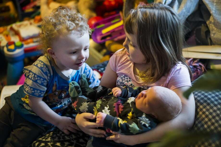 Kayson Letts, 2, left, looks at his newborn baby brother, Kyler William Letts, as he is held by their older sister Mackenzie, 7, right, Tuesday, Jan. 5, 2021 at their home in Midland. Kyler was born at 4:36 p.m. on Jan. 1, making him the first baby born in Midland in 2021. (Katy Kildee/kkildee@mdn.net) Photo: (Katy Kildee/kkildee@mdn.net)