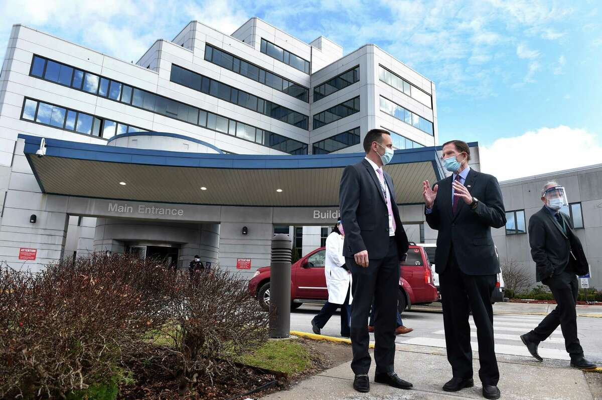 VA Connecticut Healthcare Director Alfred Montoya Jr., left, speaks with U.S. Sen. Richard Blumenthal before a press conference announcing the start of COVID-19 vaccinations for veterans at the Veteran's Affairs medical center in West Haven Jan. 5, 2021.