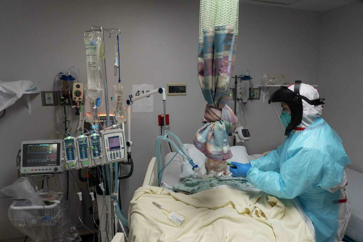 Medical staff member Gabriel Cervera Rodriguez treats a patient in the COVID-19 intensive care unit (ICU) on New Year's Eve at the United Memorial Medical Center on December 31, 2020 in Houston, Texas. According to reports, Texas has reached over 1,760,000 cases, including over 27,800 deaths. (Photo by Go Nakamura/Getty Images)