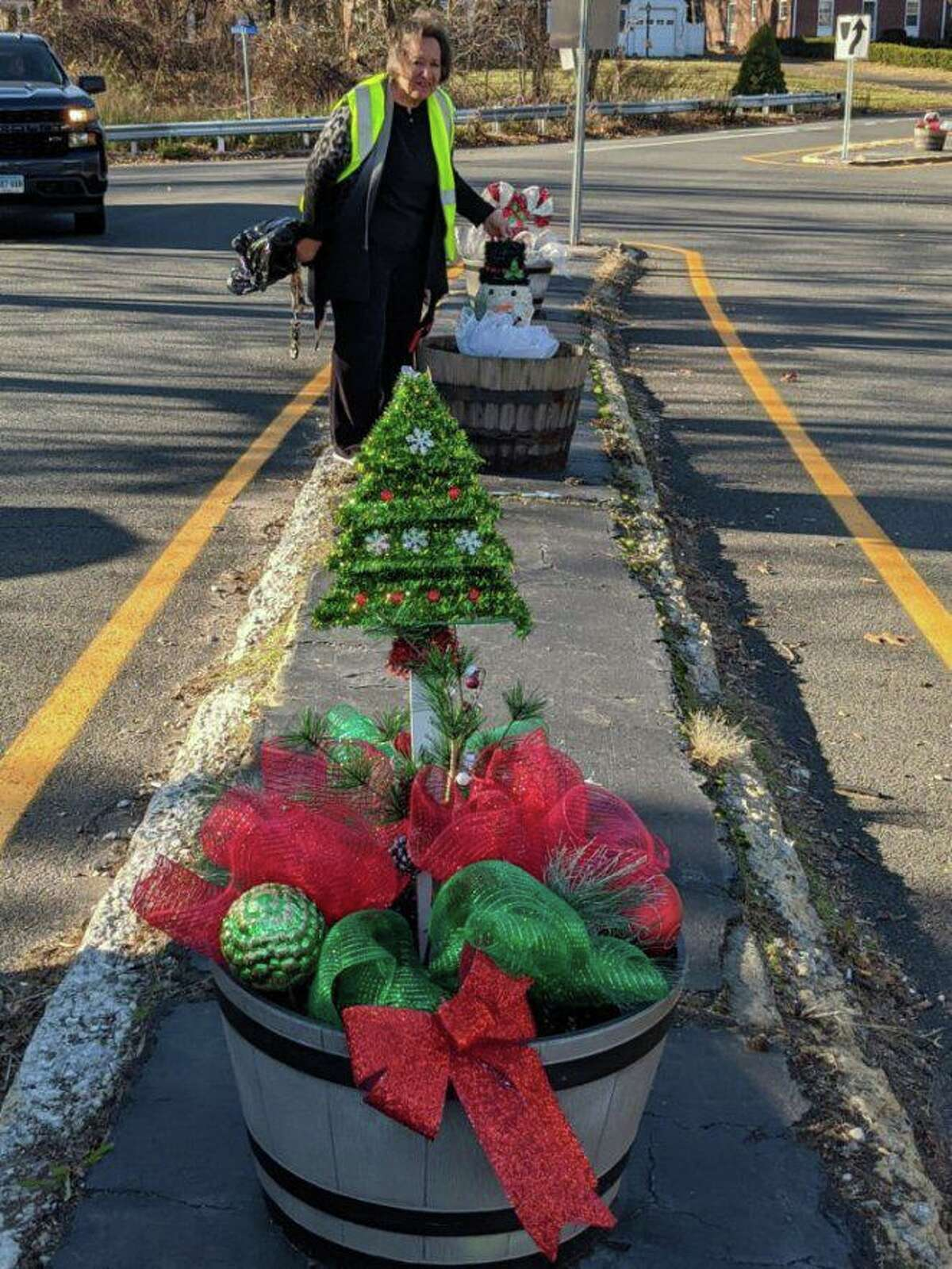 Members of the North Haven Garden Club provided holiday decorations in barrels and pots around town. Above, member Gerri Giordano works on Maple Avenue.