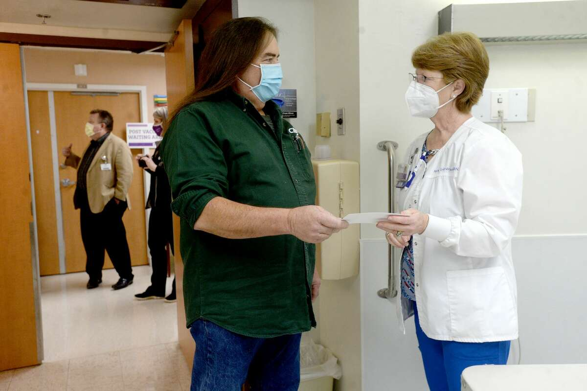 Nurse Robin Gail Wooten jokes with staff member Beau Gloor after giving him one of the first COVID-19 vaccinations at Christus of Southeast Texas Jasper Memorial Hospital Tuesday. Photo taken Tuesday, January 5, 2021 Kim Brent/The Enterprise