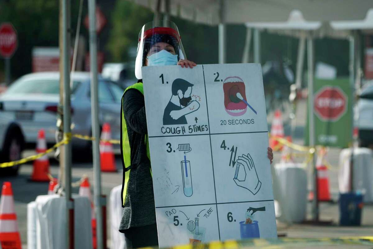 A worker gives instructions to motorists at a COVID-19 testing site Tuesday, Jan. 5, 2021, in Los Angeles.
