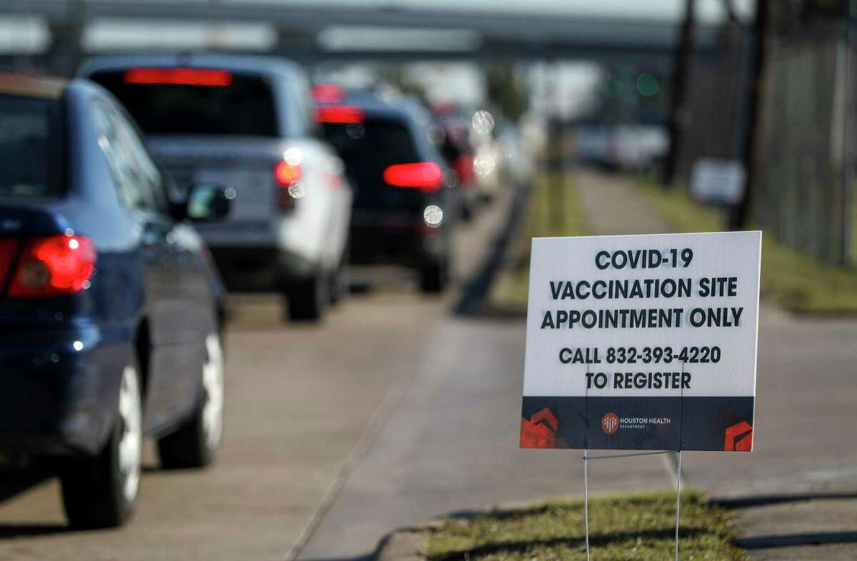 People wait in a line for a COVID-19 vaccine shot Monday, Jan. 4, 2021, near the Bayou City Event Center in Houston.