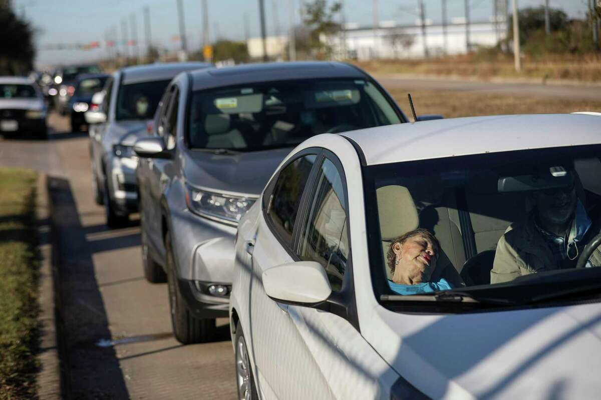 Carmen Acosta, 86, rests as she waits in line for a COVID-19 vaccine shot with her son Robert Acosta, right, and husband Luis Acosta, 91, in back seat, on Monday, Jan. 4, 2021, near the Bayou City Event Center in Houston. The son said they had been waiting about 45 minutes.