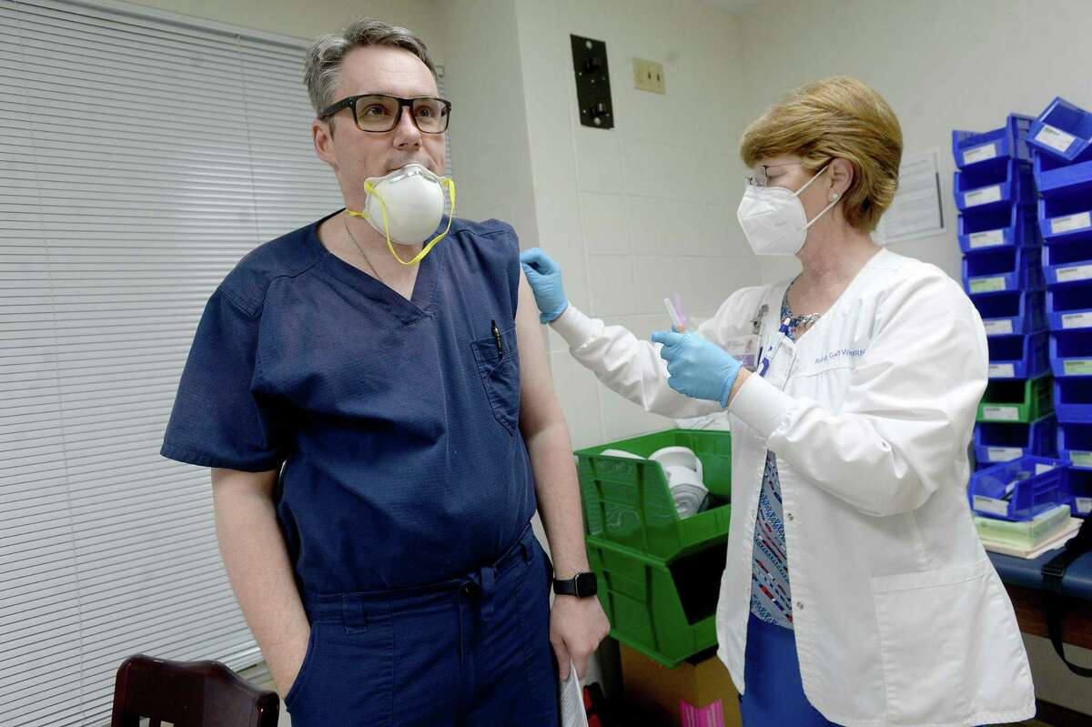Emergency Room Dr. Nicolas Ellis gets the first COVID-19 vaccination from infection control nurse Robin Gail Wooten at Christus of Southeast Texas Jasper Memorial Hospital Tuesday. Photo taken Tuesday, January 5, 2021 Kim Brent/The Enterprise