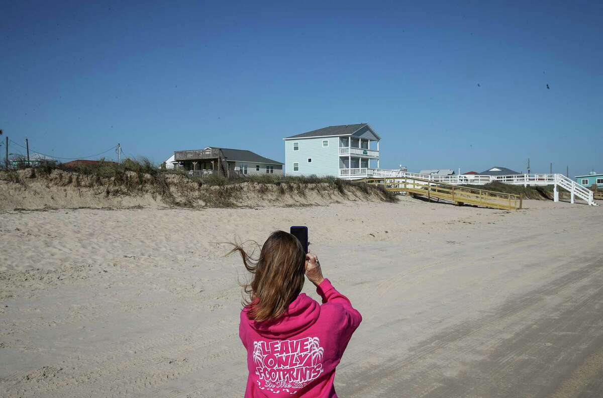 Toni Capretta, president of Save Our Beach Association, takes photos of storm-damaged dunes to send to the GLO on Tuesday, Jan. 5, 2021, in Surfside Beach.