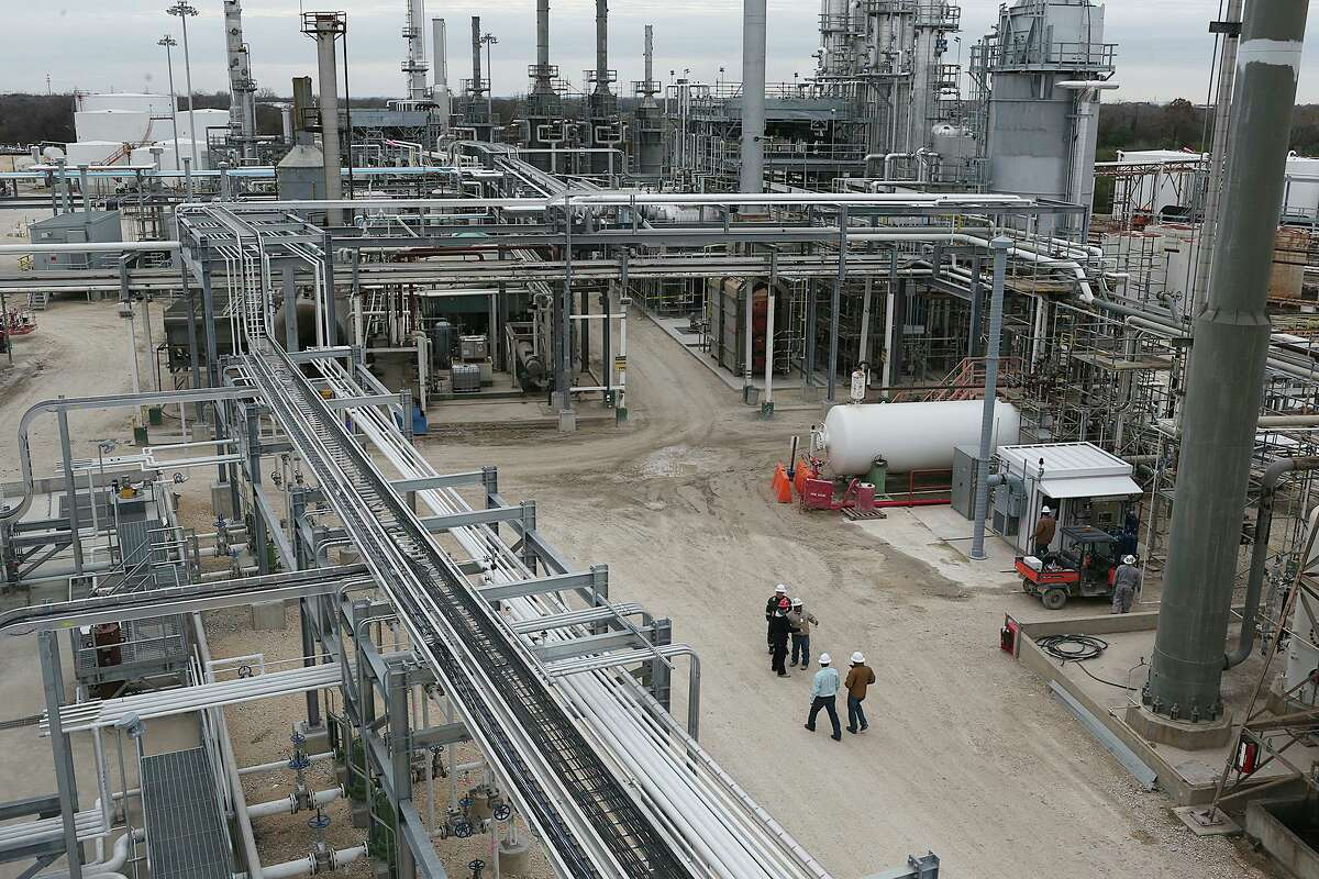 Workers gather by fractionation towers at the Calumet Refinery, Monday, Jan. 11, 2016. The refinery's operator, Lazarus Energy Holdings, said it was laying off the facility's workforce come February, though they may be re-hired.