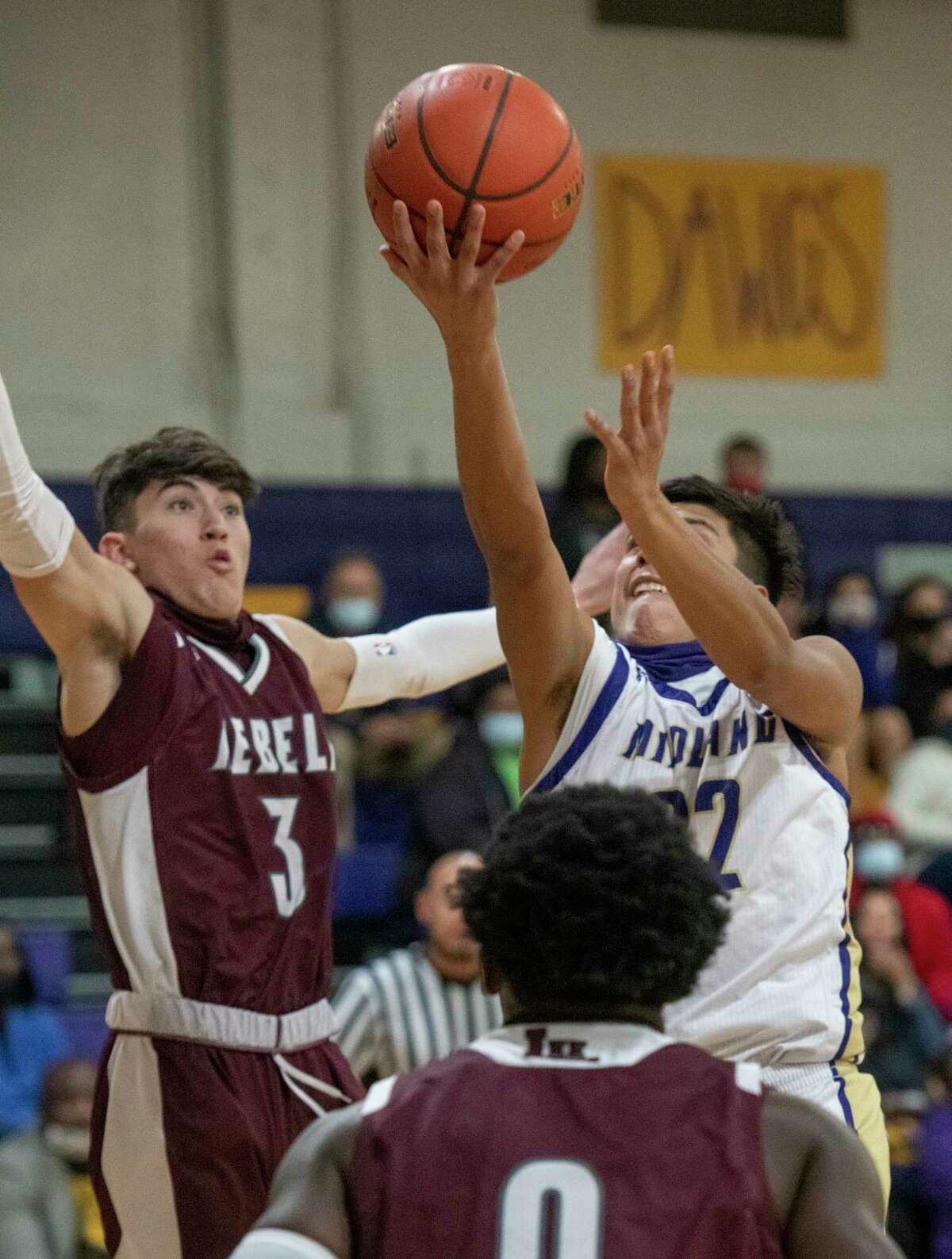 Midland High's Jaime Puentes puts up a shot as Lee High's Nate Suttle looks to block 01/05/2021 at the Midland High gym. Tim Fischer/Reporter-Telegram