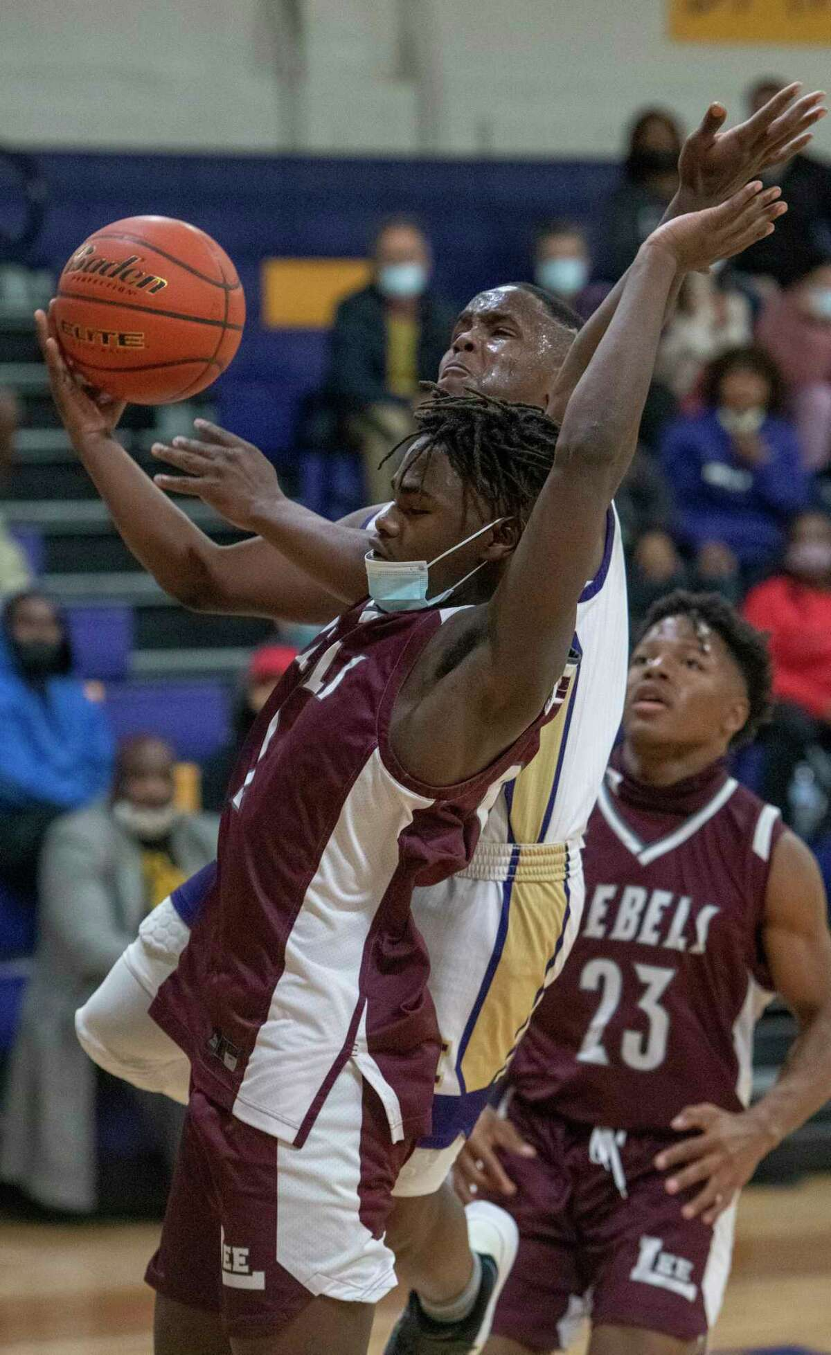 Lee High's Addison Akbar is called for a foul as Midland High's Da'Vion Mosley drives to the basket 01/05/2021 at the Midland High gym. Tim Fischer/Reporter-Telegram