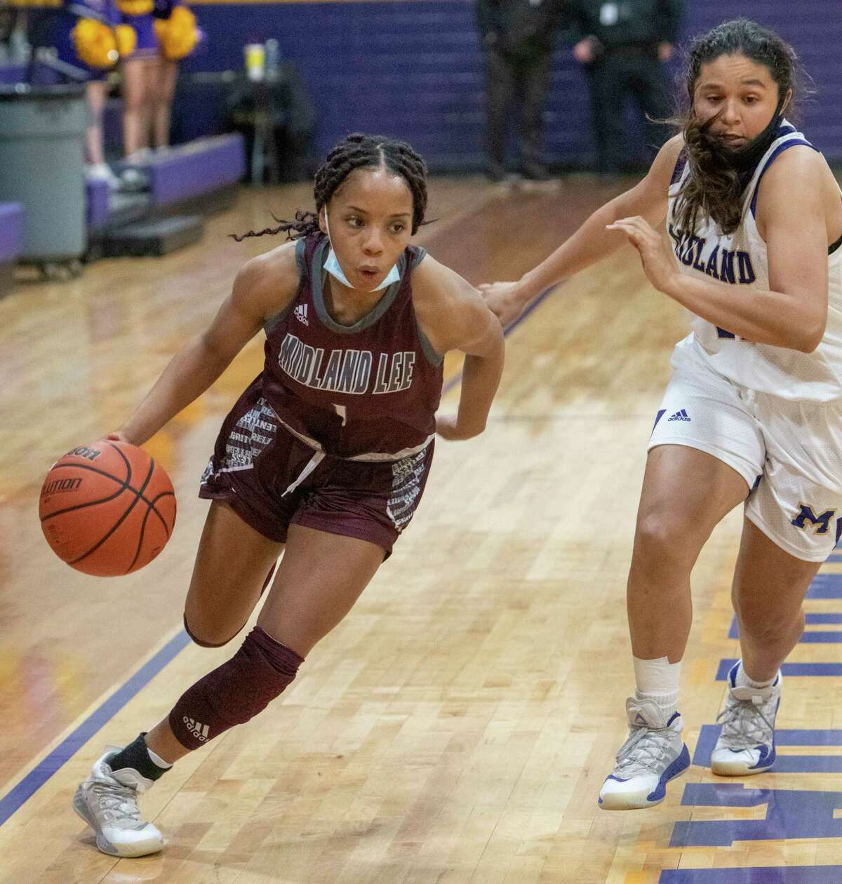 Lee High's Myleah Young drives down the sideline as she gets around Midland High's Noemi Areiga 01/05/2021 at the Midland High gym. Tim Fischer/Reporter-Telegram