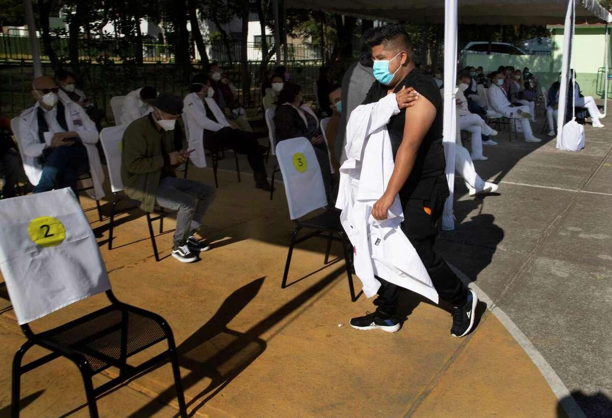 Un trabajador de la salud sostiene su brazo donde recibió una inyección de la vacuna Pfizer-BioNTech para el COVID-19 antes de tomar asiento en un área de observación en la base militar N-1 en la Ciudad de México, el miércoles 30 de diciembre de 2020.