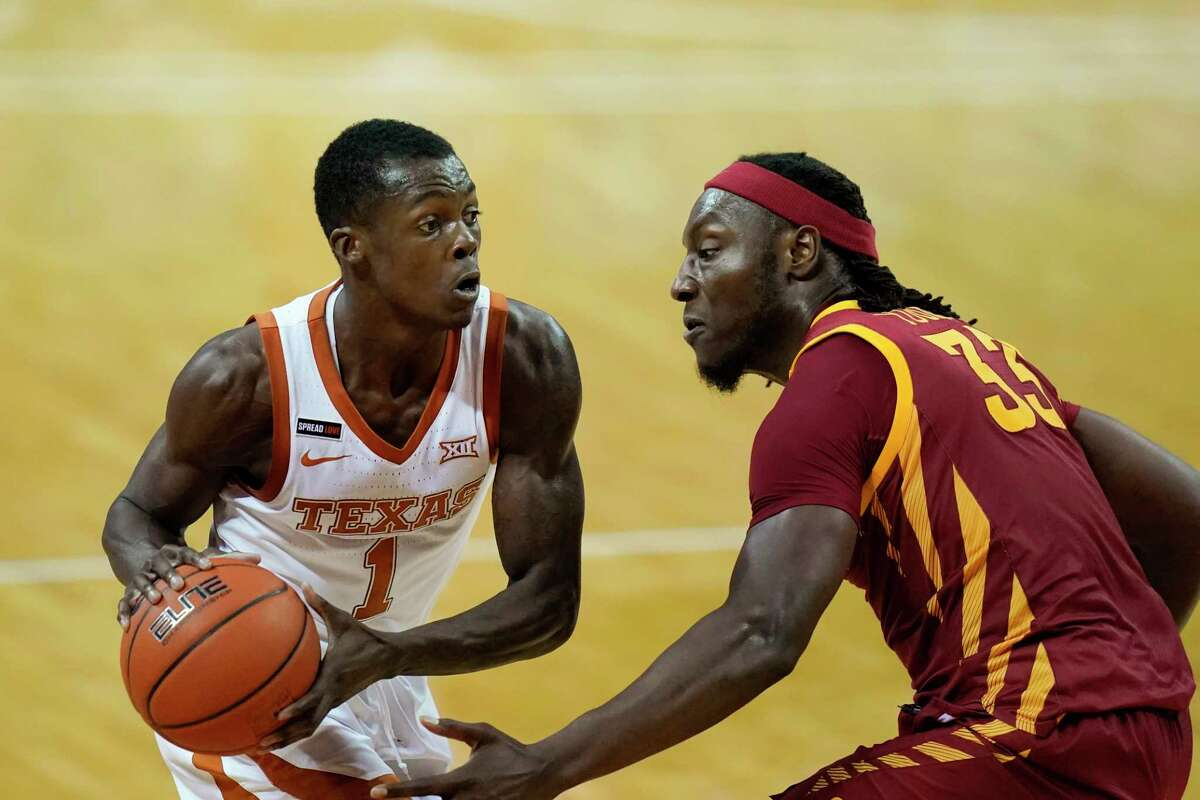 Texas guard Andrew Jones looks to pass around Iowa State forward Solomon Young, right, during the first half of an NCAA college basketball game, Tuesday, Jan. 5, 2021, in Austin, Texas. (AP Photo/Eric Gay)