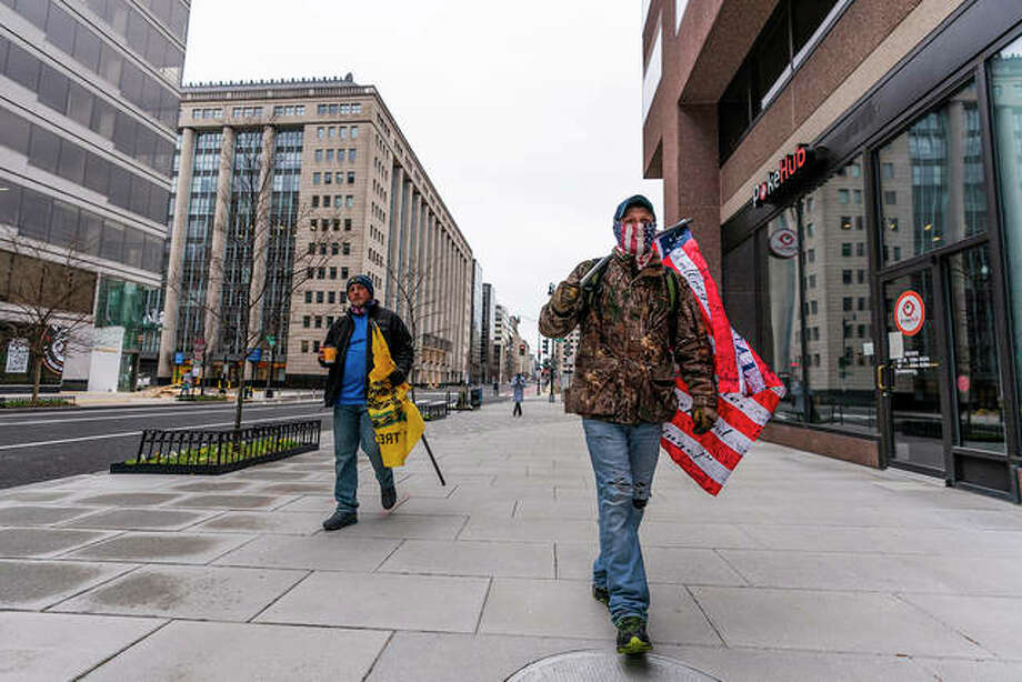 Justine Lagesse of southern Illinois carries a flag Tuesday as he walks along an almost-empty street in downtown Washington, D.C. He said he is there to support President Donald Trump. Tens of thousands of Trump supporters are expected to gather in Washington today as lawmakers confirm the election of Joe Biden as president. Photo: Manuel Balce Ceneta | AP