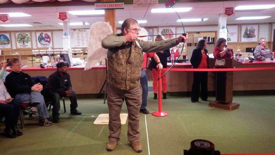 """Tom Lounsbury, wearing """"cupid-wings,"""" takesaim during the annual""""Hot Shot"""" archery contest in a past year at Bronner'sChristmas Wonderland in Frankenmuth. (Photo provided/Tom Lounsbury)"""
