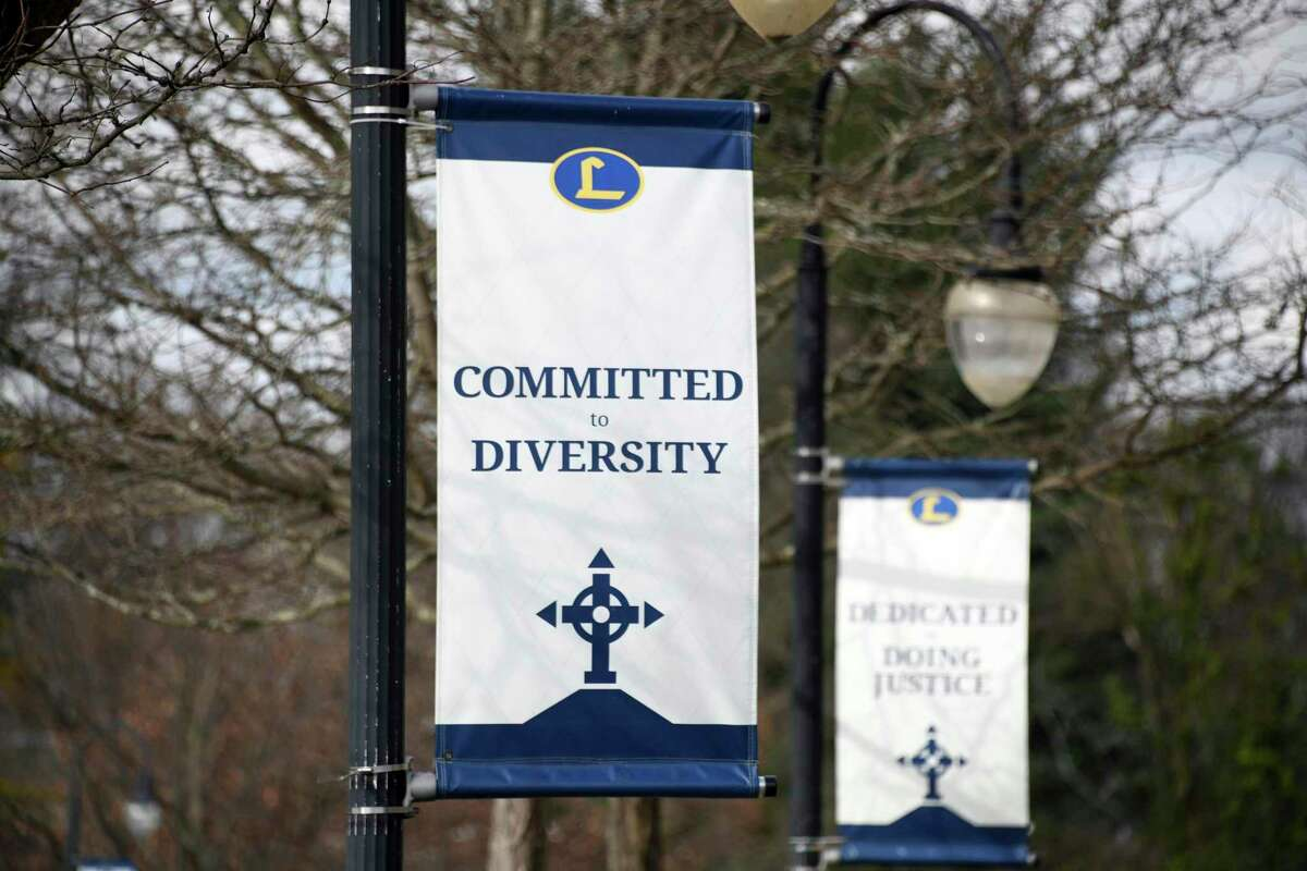 """Banners like one bearing the words """"Committed to Diversity"""" are displayed outside Knott Hall on the campus of Loyola Blakefield, in Towson, Md., Nov. 18, 2020. In the past few months, nearly every private and parochial school in the region has confronted voices of anger from Black alumni and calls for their schools to reckon with racist pasts."""