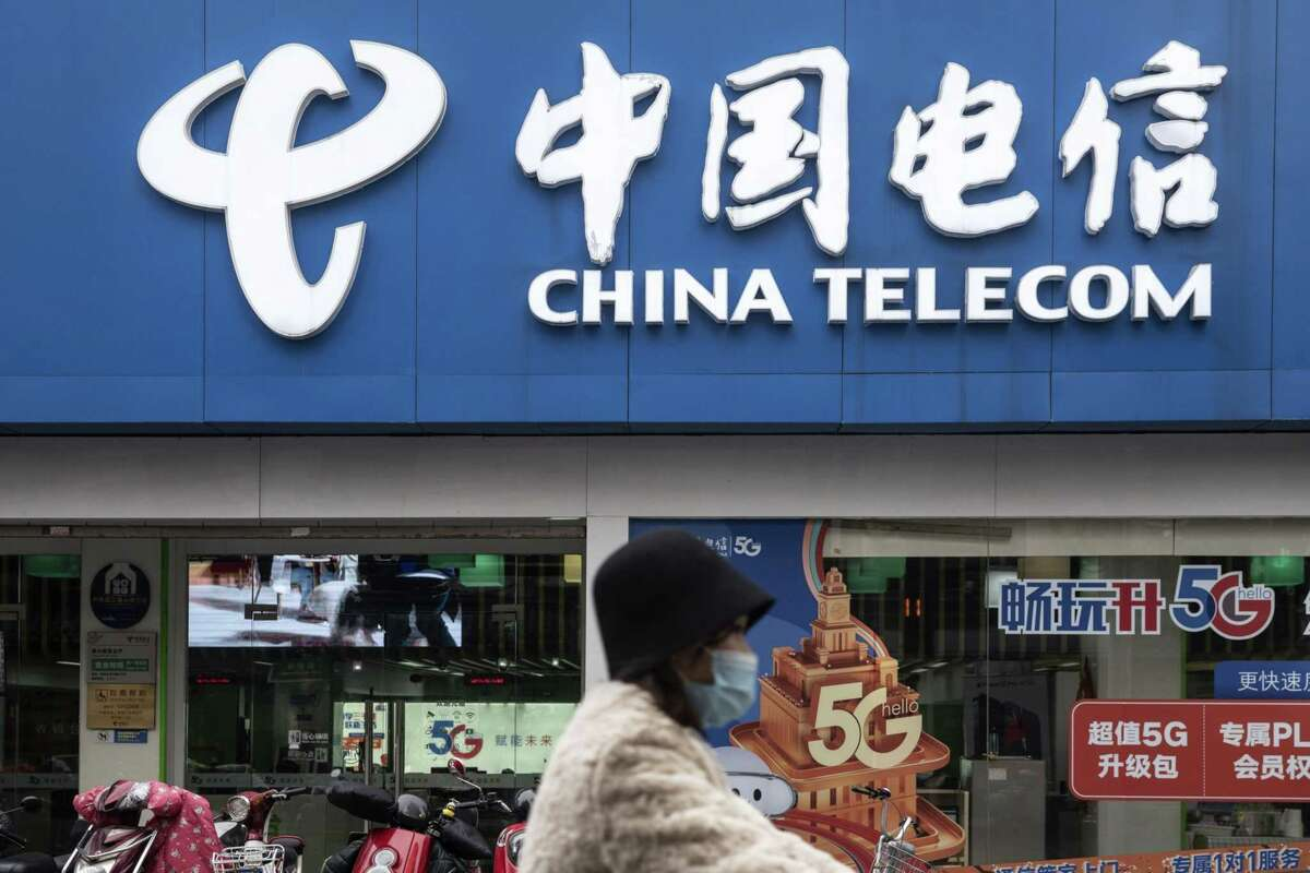A motorist wearing a protective mask travels past a China Telecom Corp. store in Shanghai on Jan. 6, 2021.