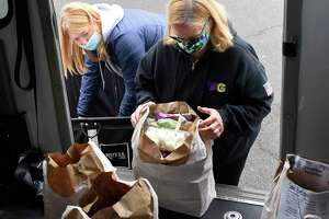 TAG assistant Sydney Orszulak, left, and TAG Executive Director Debbie Vetromile load a van with food outside the Neighbor to Neighbor headquarters at the Arch Street Teen Center in Greenwich, Conn. Monday, Dec. 21, 2020. The Transportation Association of Greenwich (TAG) has been assisting Neighbor to Neighbor's food distribution efforts and has delivered more than 100,000 pounds of food to more than 2,000 clients since the beginning of March.