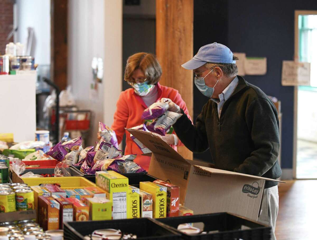 Volunteers Virginia Cheney, left, and Jim Burger sort food for Neighbor to Neighbor, which was then operating at the Arch Street Teen Center, last December. As construction work continues on the new permanent home for the nonprofit, it is moving back downtown as part of a new lease of a building in the town's Horseneck Lane parking lot.