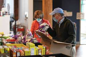 Neighbor to Neighbor volunteers Virginia Cheney, left, and Jim Burger sort food at the Neighbor to Neighbor headquarters at the Arch Street Teen Center in Greenwich, Conn. Monday, Dec. 21, 2020.