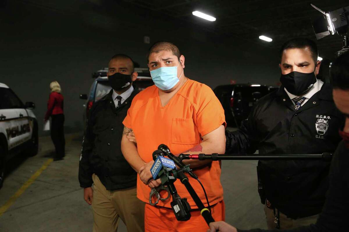 Rafael Castillo, 26, is led into the Bexar County Jail, on Dec. 16, 2020. Castillo has been charged in the murder of Nicole Perry, 31. Perry's body was found wrapped in a tarp by a cleaning crew on S. W.W. White Road on Nov. 19. Police allege believe Castillo killed Perry, with a hatchet or axe, at a home on West Harlan Avenue.