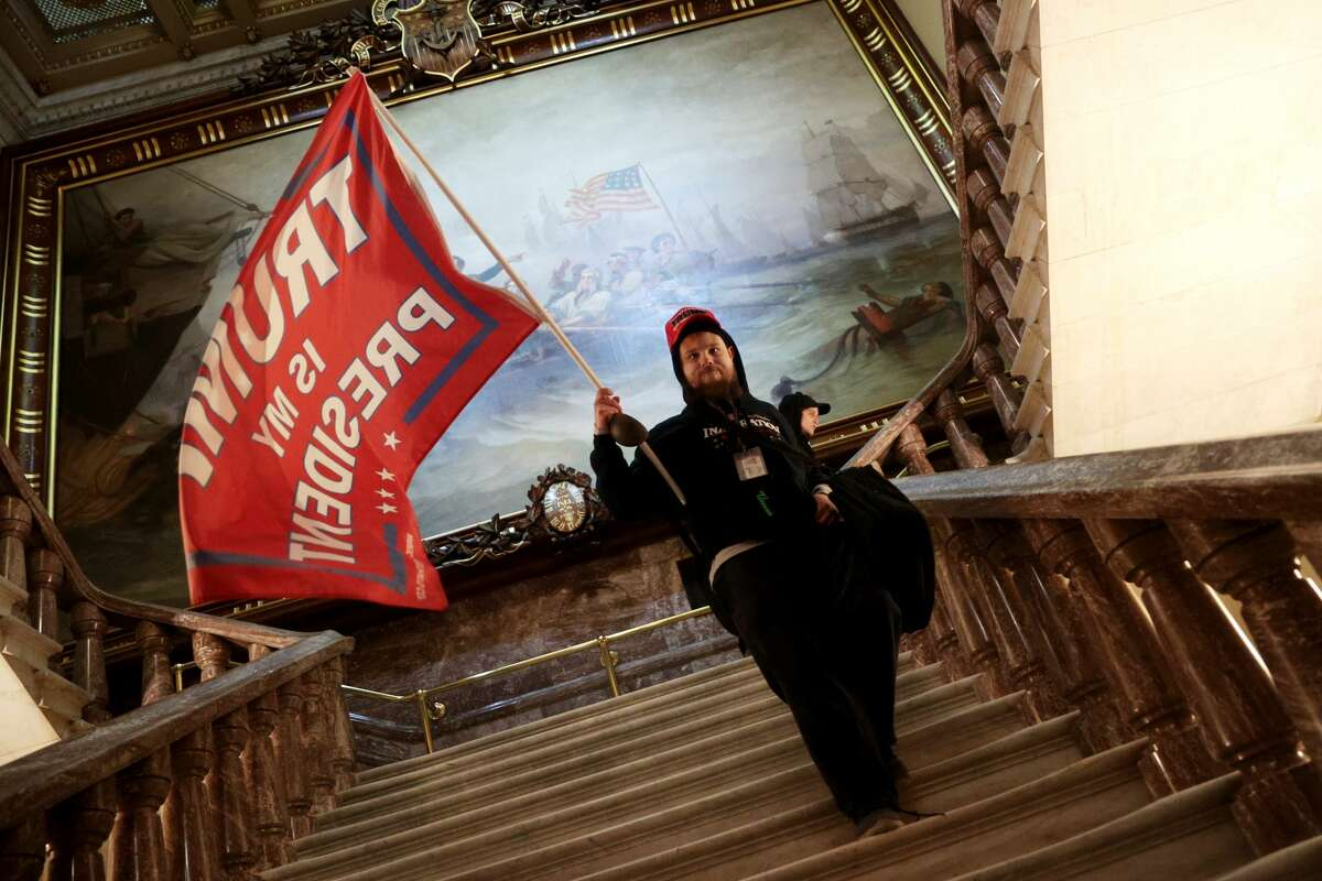 A Trump supporter holds a flag inside the U.S. Capitol Building near the Senate Chamber on Jan. 6, 2021, in Washington, DC.