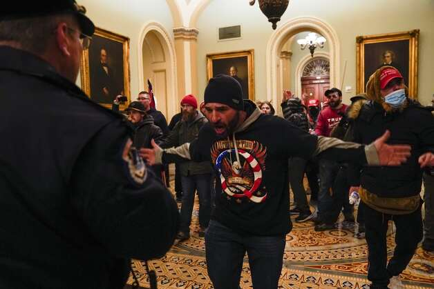 A Trump supporter gestures to U.S. Capitol Police in the hallway outside of the Senate chamber at the Capitol in Washington, Wednesday, Jan. 6, 2021, near the Ohio Clock. Photo: Manuel Balce Ceneta/AP / Copyright 2021 The Associated Press. All rights reserved.